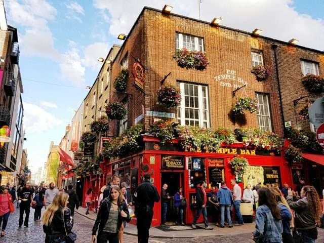 Dublin, Ireland - June 6, 2010: People can be seen on the streets outside pubs at the famous Temple Bar district of Dublin, Ireland